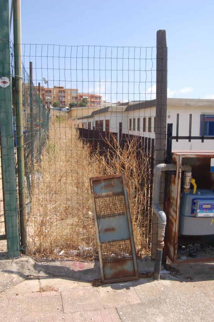 scuola Navarro erbacce a fianco dell'inferriata